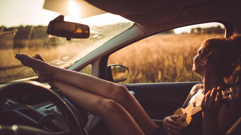 Frau sitzt bei Sonnenuntergang im Auto