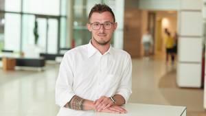HIV: Jörg Beißel steht vor einem weißen Tisch und lächelt in die Kamera