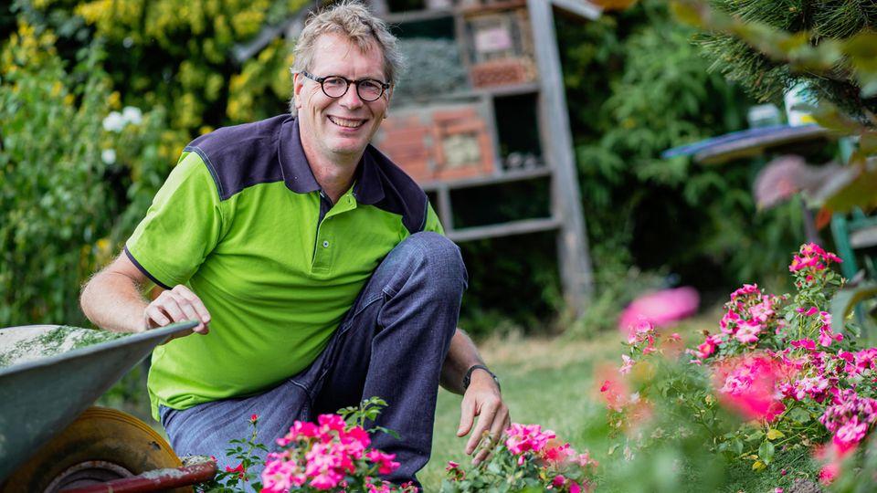 René Wadas sitzt in einem Garten vor Blumen