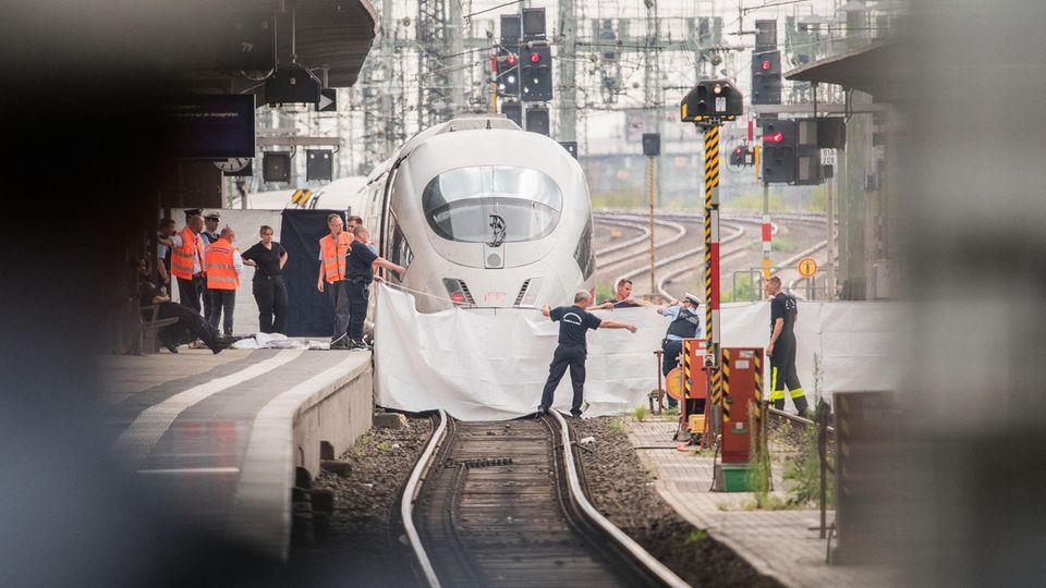 Polizisten und Feuerwehrleute spannen im Hauptbahnhof eine weiße Plane als Sichtschutz vor einen ICE