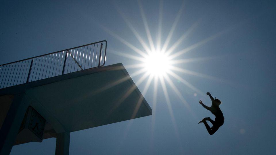 Ein Badegast springt vom 10-Meter-Turm in einem Freibad