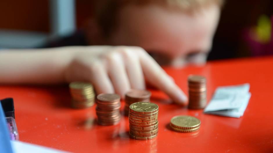 Ein Kind sitzt vor ein paar Stapeln Geldmünzen
