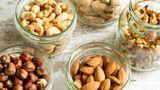 Nüsse: Schalen mit verschiedenen Nüssen stehen auf einem Tisch