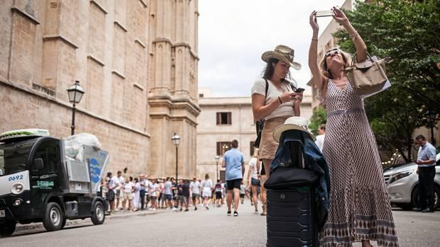 Zwei Urlauberinnen mit Gepäck und Handykamera auf dem Weg zu ihrer Unterkunft in Palma