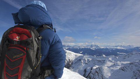 Frau in dicker Daunenjacke mit Rucksack auf dem Schrotthorn, dahinter Dolomiten mit Langkofel