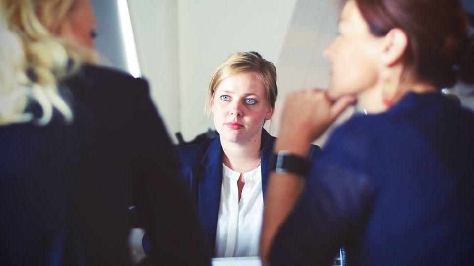 Frau sitzt im Vorstellungsgespräch gegenüber von zwei anderen Frauen