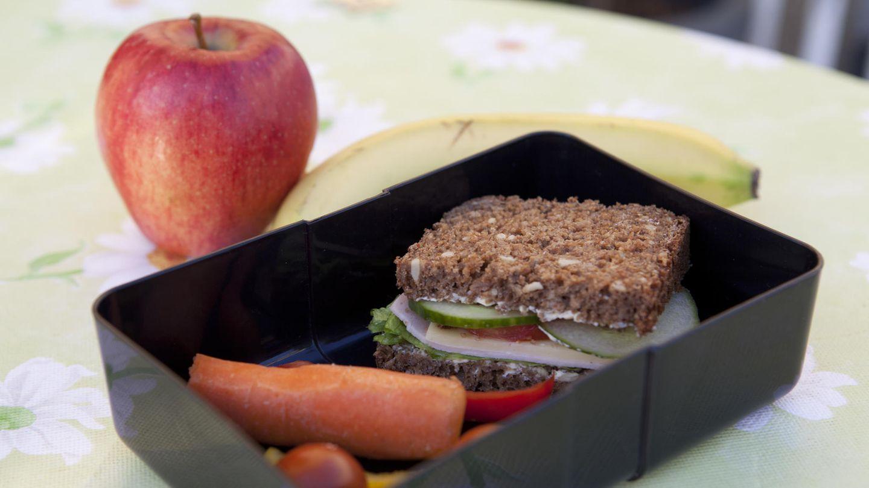 Eine Brotdose mit belegtem Brot, Obst und Gemüse