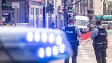 Polizeibeamte und ein Fahrzeug mit Blaulicht stehen vor einer Filiale der Frankfurter Sparkasse an der Düsseldorfer Straße. Auf die Filiale wurde ein Raubüberfall verübt.