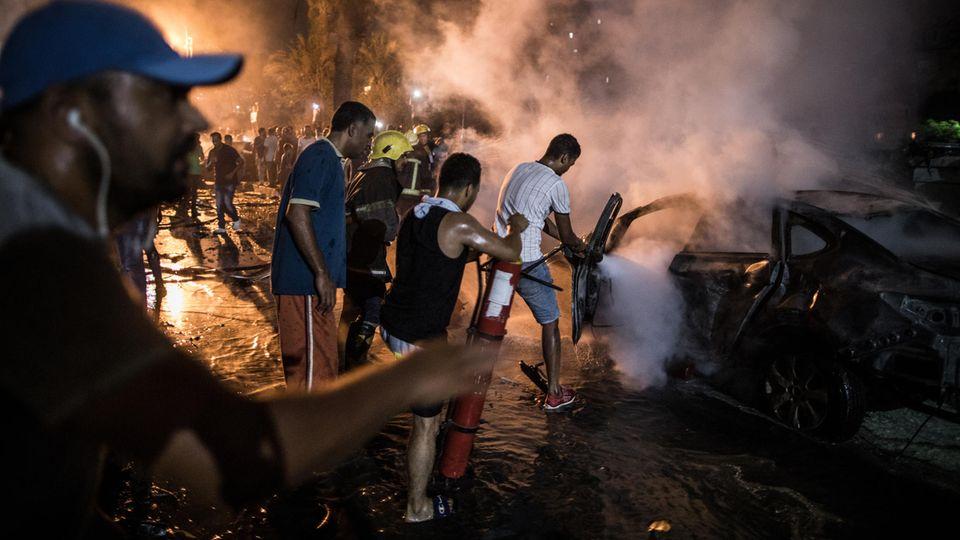 Menschen löschen ein Feuer nach einer Explosion in der Nähe des Krebsforschungsinstituts in Kairo.