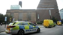 Vor einem hohen Backsteingebäude in London stehen zwei Polizeiwagen und ein Krankenwagen mit Blaulicht