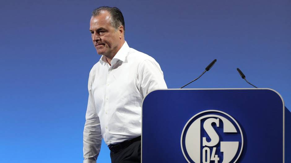 """Clemens Tönnies - in weißem Hemd und schwarzer Hose - geht vom Rednerpult mit blau-weißem """"Schalke 04""""-Logo weg"""