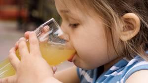 Ein dunkelblondes kleines Mädchen führt mit beiden Händen ein Glas Apfelsaft zum Mund