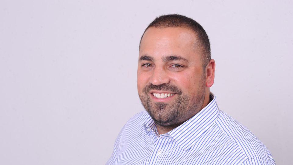 Ein etwas fülliger Mann mit kurzen Haaren und Drei-Tage-Bart lächelt in die Kamera. Er trägt ein blau-weiß gestreiftes Hemd