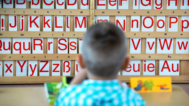 Ein Grundschüler vor einer Buchstabentafel. Für mancheMigrantenkinder ist die erste Klasse der erste intensive Kontakt mit der deutschen Sprache