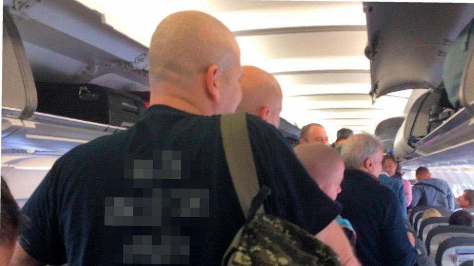 Kräftige, kahl rasierte Männer im Flugzeug