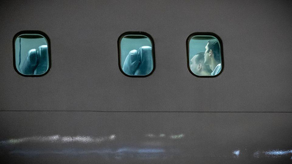 Blick von außen auf ein Flugzeug, hinter den Scheiben sind Menschen zu sehen