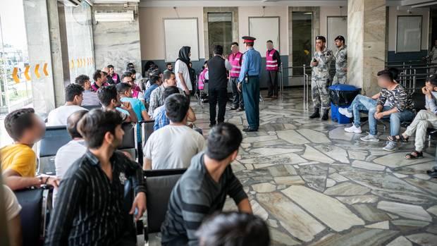 Afghanen sitzen nach ihrer Ankunft am Flughafen Kabul in einem Raum des Airports