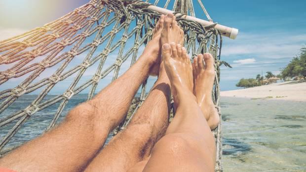 Ein Paar liegt in einer Hängematte als Symbolfoto für Urlaubsanspruch