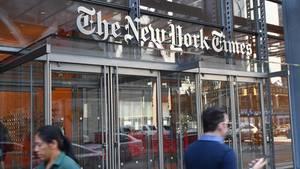 """Vor einem gläsernen Eingang unter einem """"The New York Times"""" Schriftzug laufen Menschen mit Smartphone in der Hand vorbei"""