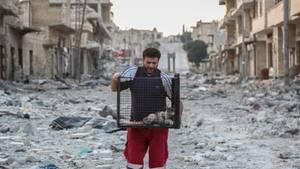"""Mohammed Alaa , auch bekannt als """"der Katzenmann von Aleppo"""", trägt einen Käfig mit einer Katze"""