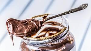 Palmöl ungesund: Ein Löffel mit Nuss-Nougat-Creme liegt auf einem Glas
