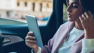 Eine Frau telefoniert mit dem Tablet auf der Rückbank eines Autos
