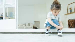 Mädchen bindet sich Schuhe