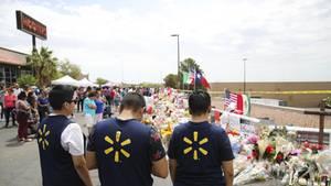 Menschen stehen vor Blumen nach Massenschiesserei