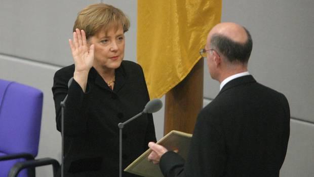 "Erster Amtseid: Merkel endet mit ""So wahr mir Gott helfe"". Bundestagspräsident Norbert Lammert hält das Grundgesetz"