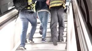 Zwei Männer in Warnwesten gehen mit einem dritten Mann gemeinsam die Treppen zu einem Flugzeug hoch.