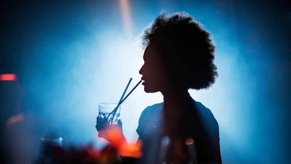 Gefahr durch K.-o.- Tropfen: Eine Frau feiert und trinkt einen Cocktail im Club