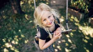 Ein Mädchen spielt an einer Schaukel