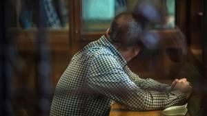 Der Angeklagte sitzt vor Beginn der Verhandlung in einem Gerichtssaal
