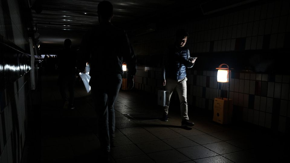 Passagiere gehen bei Stromausfall durch den notbeleuchteten Bahnhof Clapham Junction