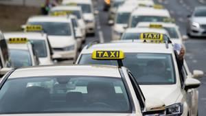 Taxen, die hintereinander und nebeneinander fahrend zwei Spuren einer Straße belegen.