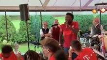 In einem Partyzelt sitzen Bayern-Spieler in roten Trikots um einen Tisch herum. Nur Alphonso Davies steht mit Mikro in der Hand