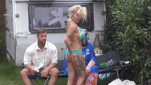 Eine blonde Frau in grün gemustertem Bikini fasst sich mit der rechten Hand an den Po