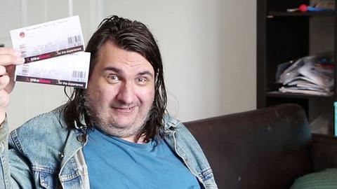Ein kräftiger Mann mit langen, schwarzen Haaren hält mit der rechten Hand zwei Tickets neben sein Gesicht