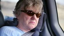 Eine Frau mit Sonnenbrille schläft im Auto