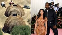 Kanye West und seine Frau Kim Kardashian posieren bei einem Event für Fotografen. Links stehen halbkugelförmige Häuser