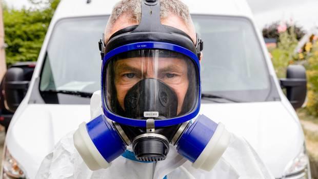 Ein Mann mit blauer Gasmaske und weißem Schutzanzug steht vor einem weißen Auto und schaut in die Kamera