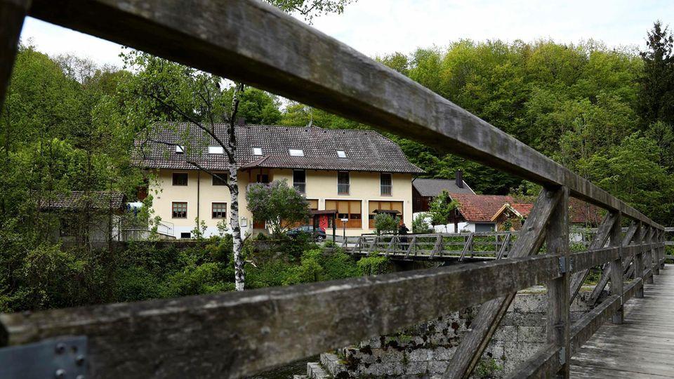 Blick durch das Geländer einer Brücke auf diePension in Passau
