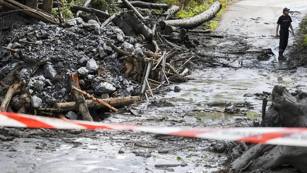 Schlamm, Bäume und Geröll bedecken eine Straße im Wallis in der Schweiz