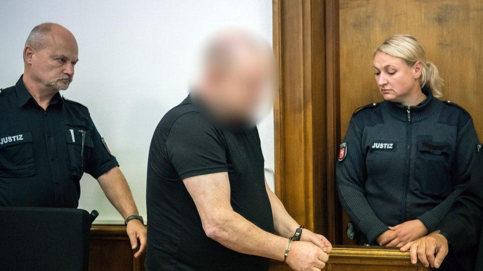 Der Angeklagte betritt zu Prozessbeginn in Handschellen den Gerichtssaal