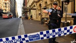 Ein Polizist steht am abgesperrten Tatort in Sydney