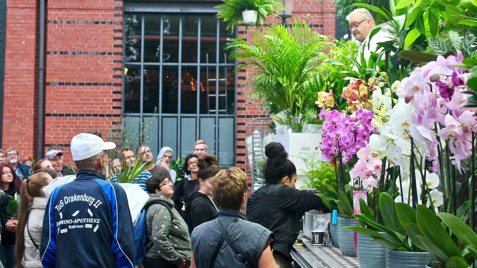 Dieter (l.) schaut sich den Blumenverkaufsstand an