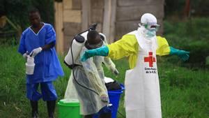 Ebola: Ein Helfer vom Roten Kreuz wird nach einem Einsatz in einem Ebola-Behandlungszentrum desinfiziert