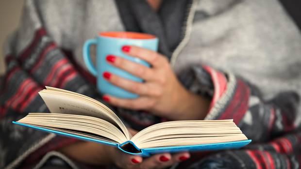 Frau mit Buch und Teebecher
