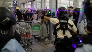 China, Hongkong: Polizisten in Schutzausrüstung stehen gegenüber Demonstranten am Haupteingang des Hongkonger Flughafen