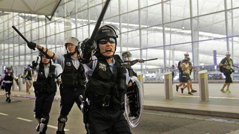 China, Hongkong: Polizisten mit Schlagstöcken schreien Demonstranten im Hongkonger Flughafen an